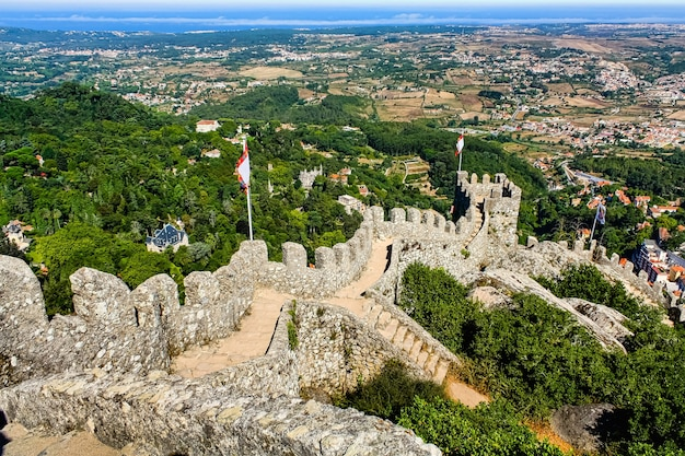 Widok z lotu ptaka na zamek sintra z miastem lizbona w tle.
