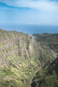 Widok z lotu ptaka na zapierający dech w piersiach krajobraz zielonych gór z opuszczoną drogą i oceanem na wyspie santo antao w republice zielonego przylądka w afryce