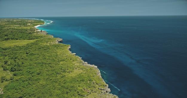 Widok z lotu ptaka na zatokę błękitnego oceanu w zielonym tropikalnym krajobrazie. zieleń trawy doliny na klifowym brzegu morza wyspy sumba, indonezja. majestatyczne wybrzeże skaliste admist z indonezyjską scenerią przyrody nikogo