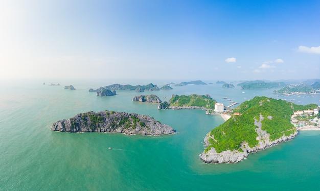 Widok z lotu ptaka na zatokę ha long z wyspy cat ba, słynnego ośrodka turystycznego w wietnamie. malownicze błękitne niebo z chmurami, wapienne skały osiągają szczyty w morzu na horyzoncie.