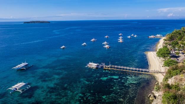 Widok z lotu ptaka na zatokę i wybrzeże w oslob, cebu, filipiny. jest to najlepsze miejsce do nurkowania z rurką i akwalungiem oraz obserwowania rekinów wielorybich.