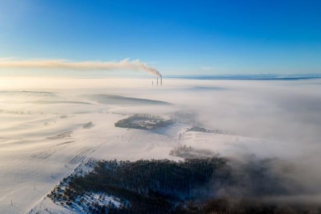 Widok z lotu ptaka na zimowy krajobraz z mglistym krajobrazem i odległymi rurami fabrycznymi emitującymi czarny brudny dym zanieczyszczający środowisko.