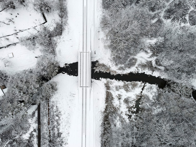 Widok z lotu ptaka na zimowy krajobraz z przejazdem kolejowym przez rzekę pokrytą śniegiem. fotografia dronów. rosyjski zimowy krajobraz. widok z góry