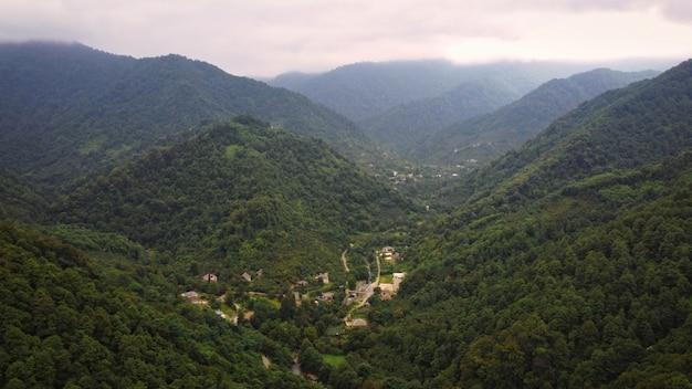 Widok z lotu ptaka natury w dolinie georgia z wąskimi zboczami wzgórz rzeki i wioski