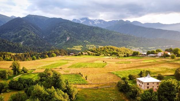Widok z lotu ptaka natury w gruzji o zachodzie słońca w dolinie wioski z polami, górami i wzgórzami