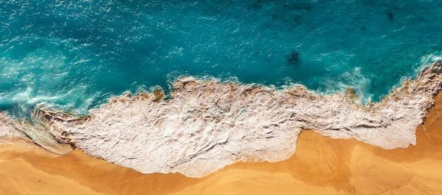 Widok z lotu ptaka niebieskich fal oceanu na plaży kelingking, wyspa nusa penida na bali, indonezja. piękna piaszczysta plaża z błękitnym morzem. samotna piaszczysta plaża z pięknymi falami. seascape tło. panorama