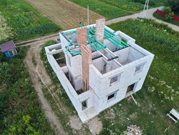 Widok z lotu ptaka niedokończonej ramy prywatnego domu z lekkimi ścianami z betonu komórkowego i drewnianymi belkami dachowymi w budowie.