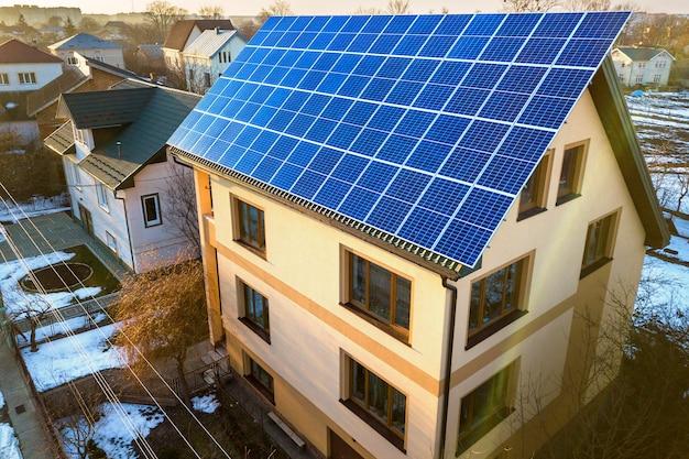 Widok z lotu ptaka nowego domu z niebieskim panelami słonecznymi fotowoltaicznymi