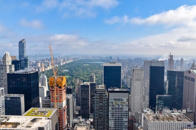 Widok z lotu ptaka nowego jorku z drapaczami chmur, budynkami w budowie i central parkiem w tle. słoneczny dzień z pewnymi chmurami. pojęcie podróży i konstrukcji. nyc, usa.