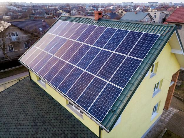 Widok z lotu ptaka nowego nowoczesnego domku mieszkalnego z niebieskim błyszczącym systemem fotowoltaicznym paneli słonecznych na dachu. koncepcja produkcji ekologicznej zielonej energii odnawialnej.