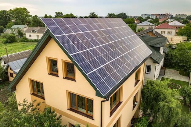 Widok z lotu ptaka nowego nowoczesnego domku mieszkalnego z niebieskim błyszczącym systemem fotowoltaicznym paneli słonecznych na dachu