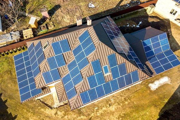 Widok z lotu ptaka nowego nowoczesnego domku mieszkalnego z niebieskim błyszczącym systemem fotowoltaicznym paneli słonecznych na dachu.