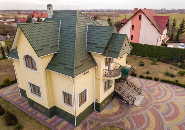 Widok z lotu ptaka nowy dom mieszkalny domek z gontem dachu na ogrodzony duży dziedziniec w słoneczny dzień.