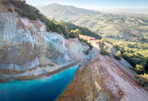Widok z lotu ptaka opuszczonej kopalni odkrywkowej alestos na cyprze. błękitne jezioro i kolorowe skały bogate w złoża miedzi i siarczków