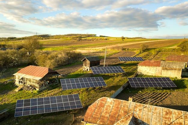 Widok z lotu ptaka paneli słonecznych w zielonym wiejskim podwórzu.