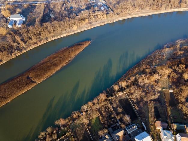 Widok z lotu ptaka, panorama wsi mała wyspa z suchą trawą w spokojnej rzece w słoneczny dzień. fotografia dronów.