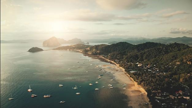 Widok z lotu ptaka pejzaż molo w świetle słonecznym. łodzie, statki, statki na płytkich wodach zatoki oceanicznej.