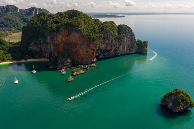 Widok z lotu ptaka pejzaż morski phra nang cave plaża z tradycyjnym długim ogonem łodzi żeglującej po morzu w ao phra nang beach, railay bay, krabi, tajlandia.