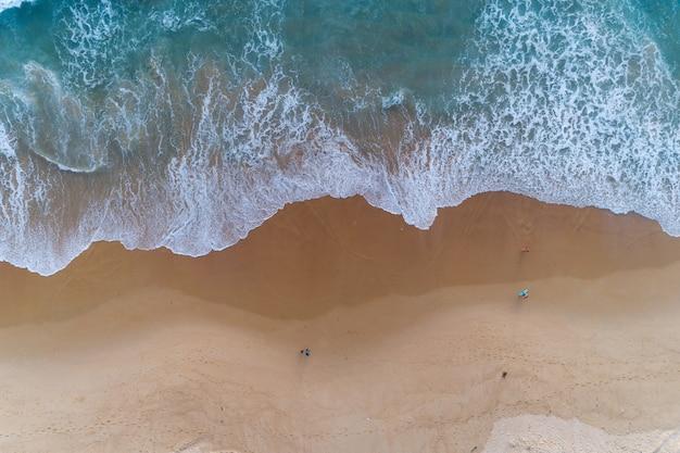 Widok z lotu ptaka piaszczystej plaży i rozbijających się fal na piaszczystym brzegu