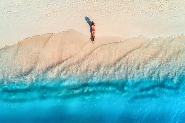 Widok z lotu ptaka pięknej młodej kobiety leżącej na białej, piaszczystej plaży w pobliżu morza z falami o zachodzie słońca. letnie wakacje. widok z góry na sportową szczupłą dziewczynę, czysta lazurowa woda. seksowne pośladki. zrelaksować się