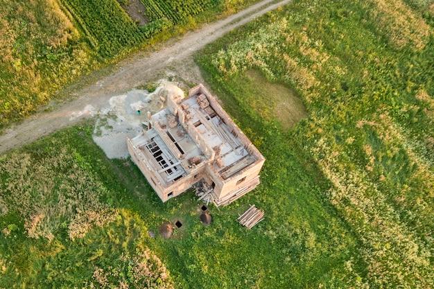 Widok z lotu ptaka placu budowy dla przyszłego domu, ceglanej podłogi piwnicy i stosów cegły do budowy.