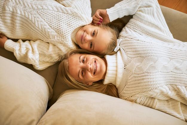 Widok z lotu ptaka pod dużym kątem, szczęśliwej, szczęśliwej młodej europejki i jej uroczej córeczki w białych swetrach, leżących wygodnie na sofie, łeb w łeb, z radosnymi uśmiechami