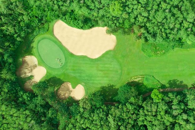 Widok z lotu ptaka pole golfowe z golfistami stawia piłkę golfową na zieleni