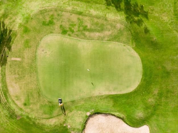 Widok z lotu ptaka pole golfowe, zielona trawa na polu golfowym ze ścieżką do wózka golfowego, człowiek tnący trawę elektryczną kosiarką i flagą
