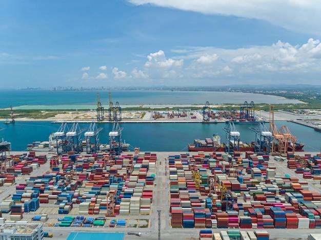 Widok z lotu ptaka portu przemysłowego z kontenerami, duży kontenerowiec wyładowany w porcie.