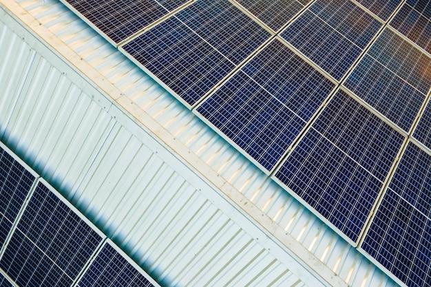 Widok z lotu ptaka powierzchni niebieskich fotowoltaicznych paneli słonecznych zamontowanych na dachu budynku do produkcji czystej ekologicznej energii elektrycznej. produkcja koncepcji energii odnawialnej.
