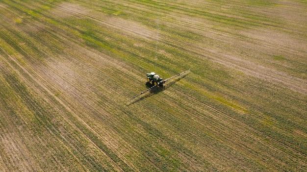 Widok z lotu ptaka pracuje na zielonym polu opryskiwanie maszyna.