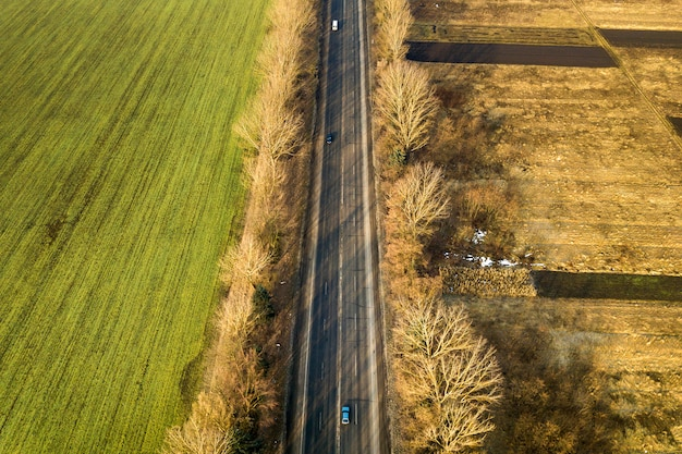 Widok z lotu ptaka prosta droga z poruszającymi się samochodami, drzewami i zieleni polami na słonecznym dniu. fotografia dronów.