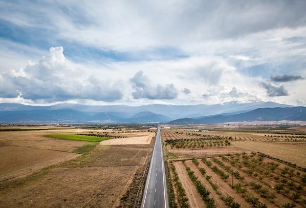 Widok z lotu ptaka prosto smołowanej drogi przez guadix, granada. w tle sierra nevada