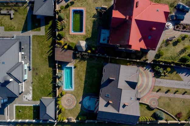 Widok z lotu ptaka prywatnego domu z utwardzonym podwórkiem z trawnikiem z zielonej trawy z betonową posadzką i basenem
