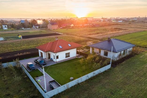 Widok z lotu ptaka prywatnych domów na wiejskich obszarach podmiejskich o zachodzie słońca.