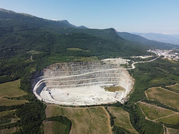 Widok z lotu ptaka przemysłowy kamieniołom odkrywkowy z dużą ilością maszyn w pracy kruszony kamień i