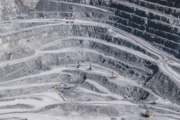 Widok z lotu ptaka przemysłowy kamieniołomu odkrywkowego z dużą ilością maszyn w pracy - widok z góry. wydobycie wapna, kredy, calx, caol