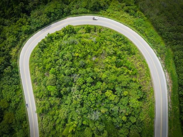 Widok z lotu ptaka przyrody lasu z samochodu na drodze na zielonym drzewie górskim, krzywa drogi widok z góry z góry, widok z lotu ptaka droga przez góry zielony las piękne świeże środowisko