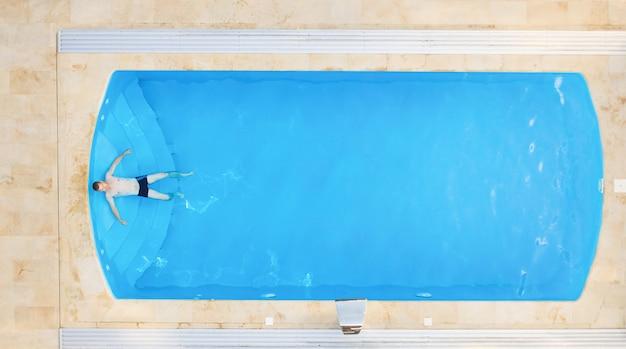 Widok z lotu ptaka relaksuje w pływackiego basenu tle młody człowiek