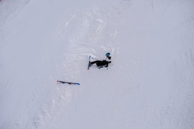 Widok z lotu ptaka rozbitego leżącego narciarza na śniegu góry.