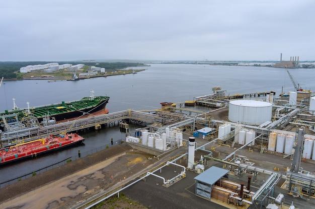 Widok z lotu ptaka rozładunek tankowca w porcie logistycznego importu eksportowego z platformami wiertniczymi, terminal naftowy marine