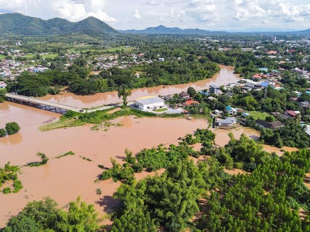 Widok z lotu ptaka rzeka powódź wieś wieś azja i drzewo leśne, widok z góry rzeka z wodą powodzi z góry, szalejąca rzeka spływająca w dół jeziora dżungli płynąca dzika woda po deszczu