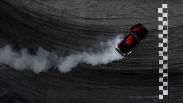 Widok z lotu ptaka samochód dryfujący na torze wyścigowym z metą i dużo dymu z płonących opon.