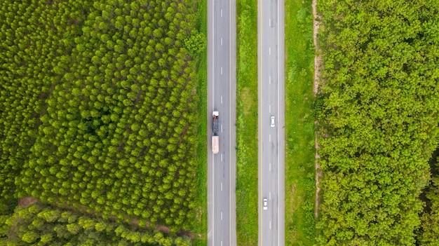 Widok z lotu ptaka samochodów i ciężarówek na drodze asfaltowej przechodzi przez zielony las