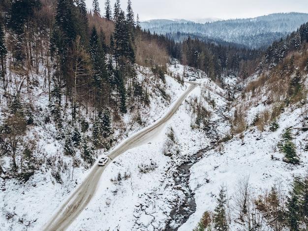 Widok z lotu ptaka samochodu poruszającego się przez kanion w zaśnieżonej zimowej przestrzeni kopii
