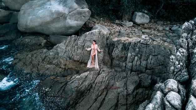 Widok z lotu ptaka: seksowne zdjęcie pięknej blondynki pozuje stojącej wśród skał w pobliżu brzegu morza z falami. zdjęcie drona. quadrocopter.