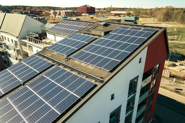 Widok z lotu ptaka słonecznych paneli fotowoltaicznych na dachu bloku mieszkalnego do produkcji czystej energii elektrycznej. koncepcja autonomicznej zabudowy.