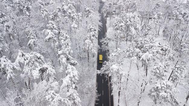 Widok z lotu ptaka śnieg zakrywał drogę w zima lesie, ciężarówka