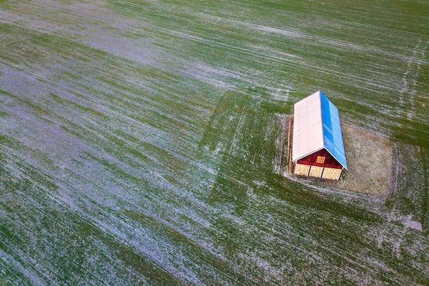 Widok z lotu ptaka stara drewniana stajnia z jaskrawym dachem w zieleni polu na pogodnym wiosna dniu. fotografia dronów.