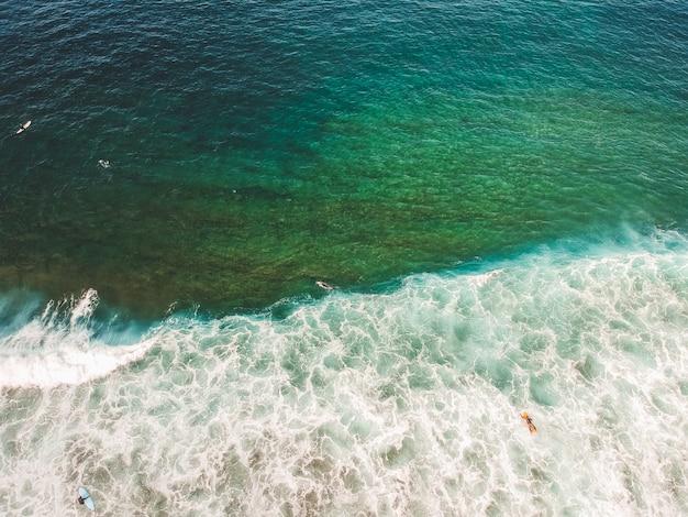 Widok z lotu ptaka surferów na falach oceanu atlantyckiego. piaszczysta plaża